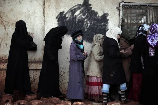 Syrian women wait outside a bakery to buy bread in Maarat Misrin, near Idlib. Elsewhere in Syria, several bomb blasts were reported Wednesday in Damascus, the capital.