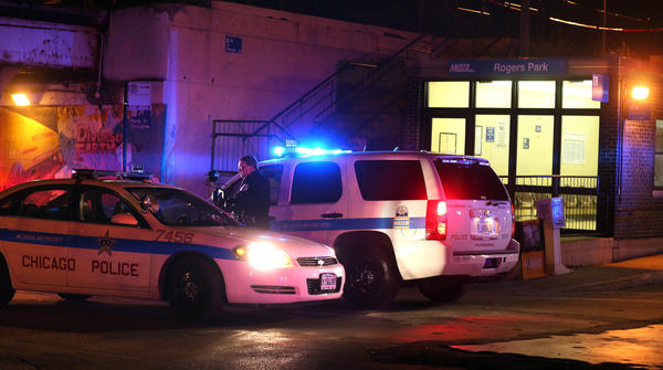 Chicago police vehicles sit outside the Rogers Park Metra station after a pedestrian was struck and killed by a Metra train.