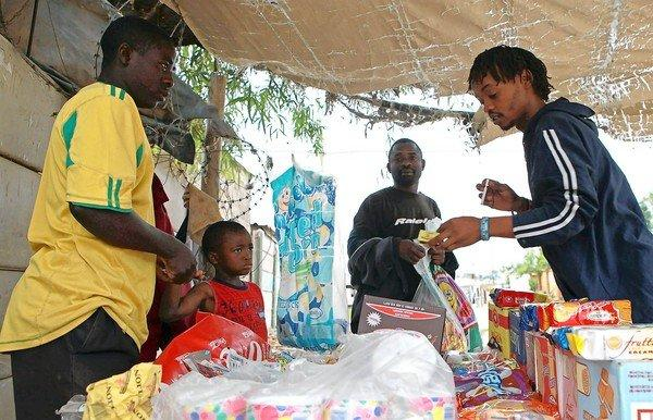 Fernando Benden, left, sells single cigarettes and sweets from his small stand in Diepsloot, South Africa.