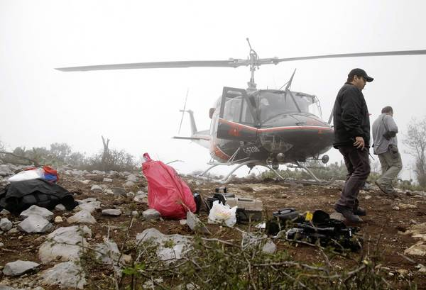 Investigators walk next to a bag that contains human remains while inspecting the site south of Monterrey, Mexico, where the plane carrying Mexican American singer Jenni Rivera crashed Sunday, killing all seven people aboard.