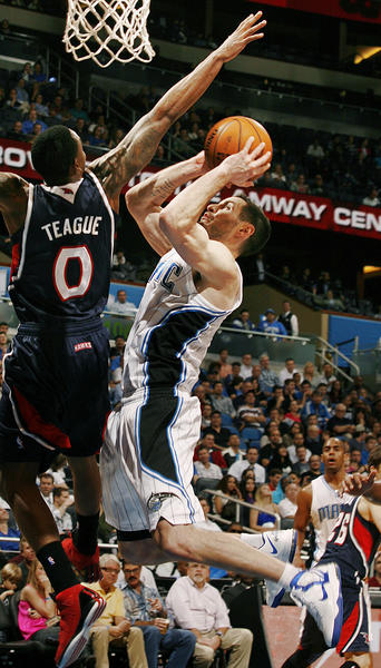 Orlando guard J.J. Redick (right) shoots under Atlanta guard Jeff Teague (0) during the Atlanta Hawks at Orlando Magic NBA game at the Amway Center on Wednesday, December 12, 2012. Atlanta won the game 86-80.