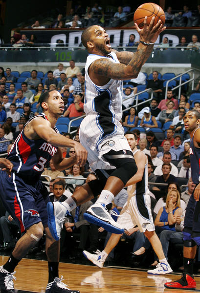 Orlando guard Jameer Nelson (14) scores in front of Atlanta guard Devin Harris (34) during the Atlanta Hawks at Orlando Magic NBA game at the Amway Center on Wednesday, December 12, 2012.