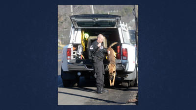 An unidentified officer from the Westmoreland County Park Police retrieves bomb-sniffing dog Rex from his traveling case before searching the Shade-Central City High School on Wednesday.