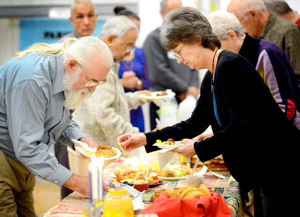 Ed Branthaver, left, and Marge Poling, right, share in the annual Interfaith Coalition Holiday Traditions Dinner Wednesday night at Hagerstown Church of the Brethren.