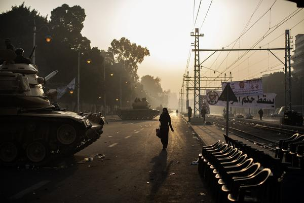 Egyptians walk past a line of army tanks stationed outside the presidential palace in Cairo on December 12, 2012. Egypt's powerful army has called for President Mohamed Morsi and the secular opposition to meet later in the day to stop a crisis over an imminent constitutional referendum from tearing the country apart.