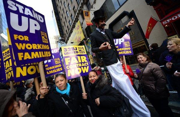 Protesters show their support for Broadway theater cleaners, porters and matrons at a demonstration in Times Square in New York. The union representing Broadway service workers is threatening a strike over healthcare benefits.