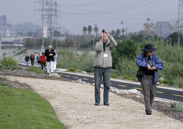Bob Thompson takes a photo while Jeanne LeFever looks around during the grand opening of the Glendale Narrows Riverwalk in Glendale. Phase 1 of the project opened Wednesday at the corner of Paula and Garden Streets in Glendale with a ribbon cutting ceremony.