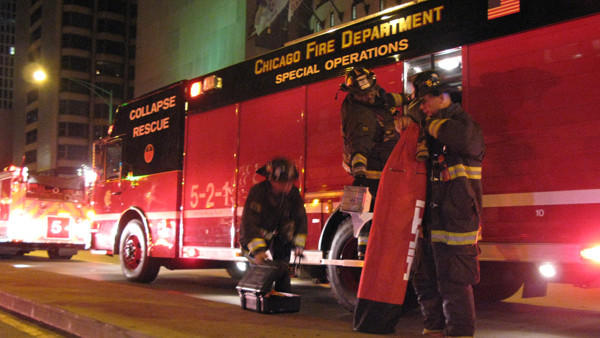 Firefighters grab equipment from inside a Collapse Rescue truck outside the Intercontinental Hotel early Dec. 13, 2012.