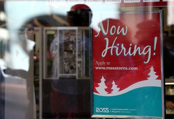 A sign advertising job openings hang in the window of a Ross clothing store in San Francisco.