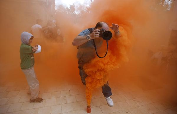 A photographer jumps over a smoke canister during a demonstration by firefighters, security and military personnel against cuts in their salaries imposed by Spanish Government, in the Andalusian capital of Seville September 29, 2012. Spain's debt will reach 90.5 percent of gross domestic product by end 2013 after hitting 85.3 percent of GDP by the end of this year, the government's budget document showed on Saturday.