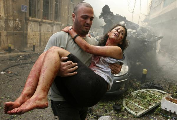 A wounded woman is carried at the site of an explosion in Ashrafieh, central Beirut, October 19, 2012. At least two people were killed and 15 wounded by a huge bomb that exploded in a street in central Beirut on Friday, witnesses and a security source said.