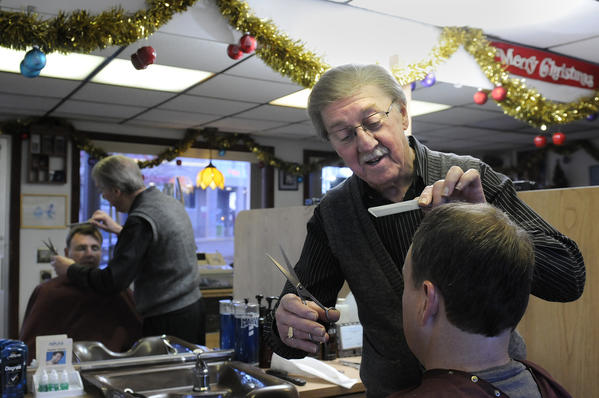 Barber Bob St. Pierre, who has worked for the past 50 years at his family-owened barbershop, The Village Hair Stylist, cuts the hair of a customer at his Main Street shop.