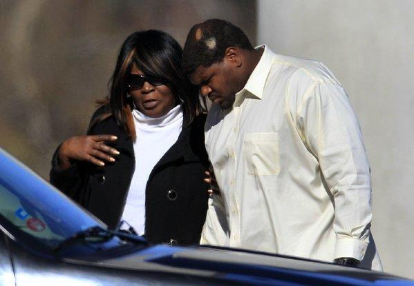 Dallas Cowboys football player Josh Brent, right, embraces an unidentified person at a memorial service Tuesday for teammate Jerry Brown.