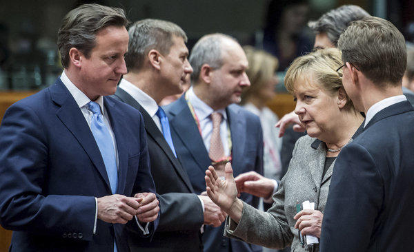 British Prime Minister David Cameron, left, speaks with Finland's prime minister, Jyrki Tapani Katainen, right, and German Chancellor Angela Merkel, second right, during a round-table meeting at a European Union gathering in Brussels.