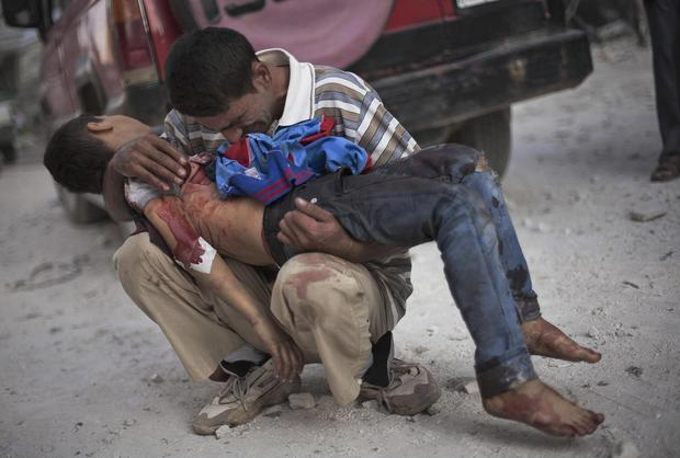 A Syrian man holds the body of his son, who was killed by government troops in Aleppo.