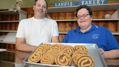 Owners Scott and Trudy Landis pose with freshly baked date nut pinwheel cookies at their Berlin Bakery on Thursday.