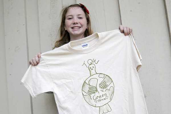 Fifth-grader Malin Glade, 11, shows off her T-shirt design for Top of the World Elementary School's Waste-Free Wednesday event.