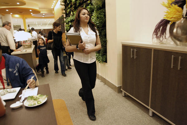 9021 Pho hostess Vanessa Williams walks customers to their table during a trial run, which took place at the Glendale Galleria on Wednesday, December 12, 2012.