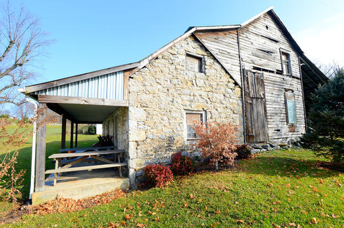 A smaller stone house at Twin Springs Farm is a simple structure. Its roof has four pitches.