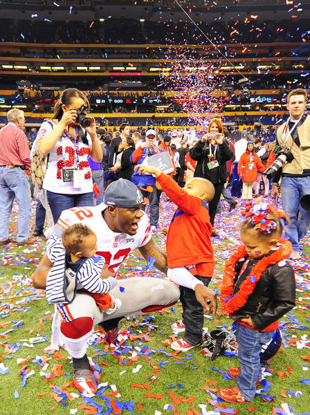 New York Giants defensive back Derrick Martin (22) celebrates with family after the Giants defeated the New England Patriots 21-17 in Super Bowl XLVI at Lucas Oil Stadium.