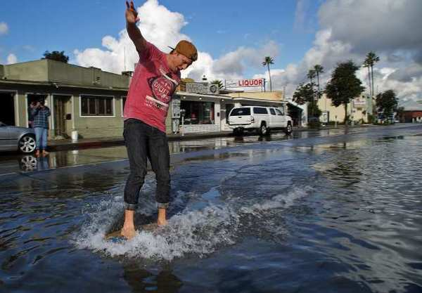 Newport Beach resident Morgan Boultinghouse rides a skimboard Thursday morning at 26th Street and Newport Boulevard, where water had amassed onto the street and city workers were pumping it back into the harbor. The area was closed to traffic for about an hour.