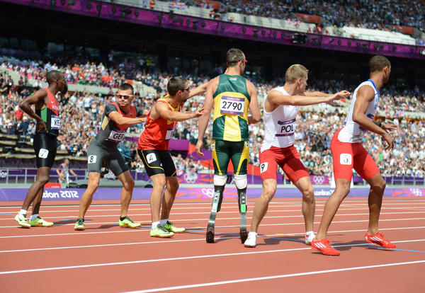 Double amputee Oscar Pistorious (RSA) waits the for the baton in the exchange zone of a men's 4 x 400m relay heat during the London 2012 Olympic Games at Olympic Stadium.