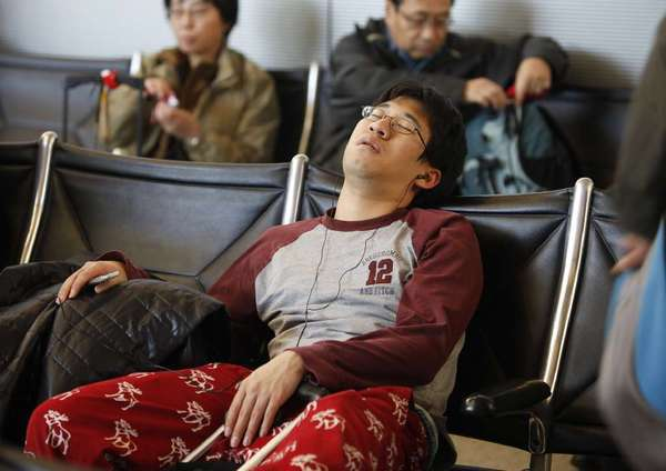 This traveler catches a nap while waiting in the international terminal at LAX on Dec. 23 last year. Although fewer people will be flying this year, planes will be fuller, because of reduced capacity.
