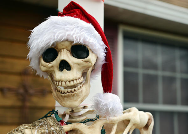 """It's left over from Halloween, but I figured I'd put a Santa hat on him."" George Weaver, of Allentown says about a skeleton siting on his front porch railing, as he hangs white and blue lights on his hedges."