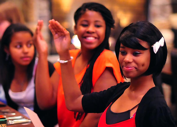 "Desire Lovelace, center, and Ziya Young, right, practice their ""princess waves"" Thursday evening as they wait for dinner to begin at LJ's & The Kat Lounge. Marlynnes Reyes watches. The girls were part of a group from the Boys & Girls Club at Noland Village who earned a meal with lessons on etiquette at the restaurant."