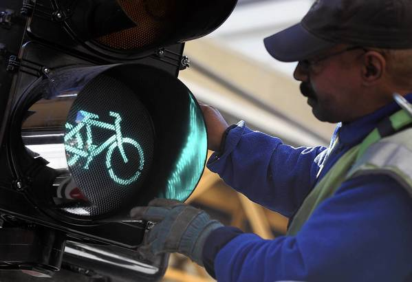 Chicago Department of Transportation worker Stanford Dorsey adjusts a bicycle traffic signal Thursday at Dearborn and Lake streets in Chicago.