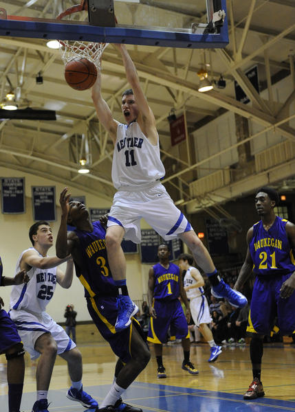 New Trier's Steven Cook dunks over Waukegan's Jachai Taylor during a boys basketball game in Winnetka, Thursday, Dec. 13, 2012.
