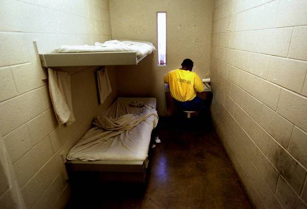 An inmate eats dinner in his cell at the Twin Towers jail in downtown Los Angeles. A Los Angeles County sheriff's jailer has been charged with assaulting two inmates, including one in the Twin Towers.