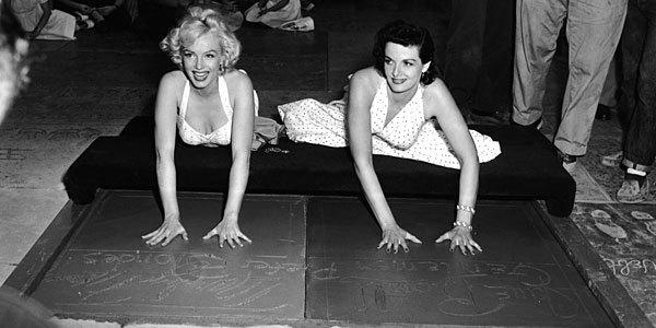 "Commemorating their movie hit ""Gentlemen Prefer Blonds"" in the favored Hollywood way, Marilyn Monroe, left, and Jane Russell plant their hands in a slab of freshly-poured cement in front of Grauman's Chinese Theater on Hollywood Boulevard. Some Van Nuys residents want a post office named after Marilyn Monroe."