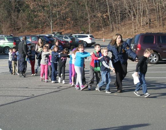 State police personnel led children from the school, following the shooting.