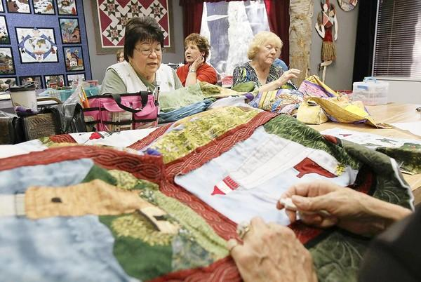 Kathy Schymick, left, Christy Carlin, center, and Sandy Miyahara, right, along with other members of the Material Girls work on making quilts at the Piecemakers Country Store in Costa Mesa on Monday.