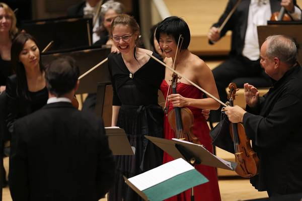 Resident composer Anna Clyne stands with violinist Jennifer Koh as Harry Bicket (left) and Jaime Laredo (right) applaud at Symphony Center in Chicago on Thursday.