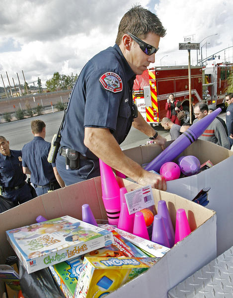 Glendale Fire paramedic Tom Nicola loads toys onto a fire department pickup in Glendale at 4Over, Inc. on Friday, December 14, 2012. Employees at 4Over, Inc. collected $5,000 in donations to purchase new toys to the 20th Annual ABC7 Spark of Love toy drive with the Glendale Fire Department.