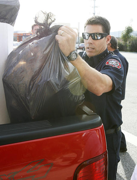 Glendale Fire paramedic Tom Nicola loads the back of an F150 with toys in Glendale at 4Over, Inc. on Friday, December 14, 2012. Employees at 4Over, Inc. collected $5,000 in donations to purchase new toys to the 20th Annual ABC7 Spark of Love toy drive with the Glendale Fire Department.