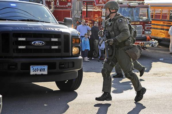 A state police SWAT team member runs to a police car during the evacuation of Sandy Hook Elementary School in Newtown, Connecticut after a gunman opened fire inside the school.