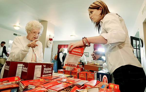 Wendy Barrick, right, outreach coordinator for Maryland Food Bank helps Betty Wolfe with food items at Francis Murphy Senior Apartments on Friday. The food bank delivered food to the residents as part of their Pantry Program.