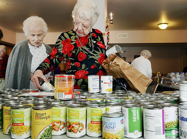 Levia Rohler, left, and Hilda Kline look over canned food at Francis Murphy Senior Apartments on Friday.  The Maryland Food Bank's Western Branch distributed the food through the Pantry Program.
