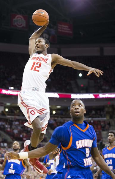 Ohio State Buckeyes forward Sam Thompson (12) goes up to dunk over Savannah State Tigers guard Cedric Smith. Ohio State won the game 85-45.
