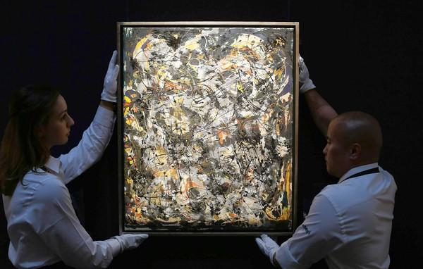 "Sotheby's employees hold Jackson Pollock's ""Number 4, 1951"" on Oct. 8, 2012, in London."