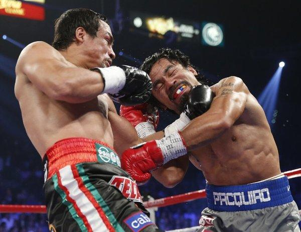 Manny Pacquiao and Juan Manuel Marquez exchange blows in their fight Saturday.