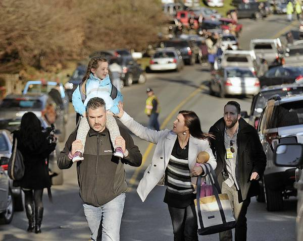 Parents leave Sandy Hook Elementary School in Newtown, Connecticut, with their children.