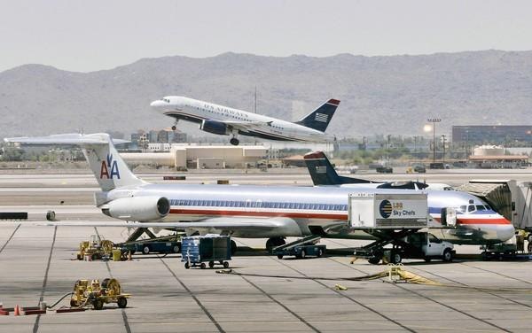 A merger of American Airlines and US Airways would form the nation's largest airline with up to 1,500 planes in its main line and regional fleets and more than 120,000 employees. Above, a US Airways jet takes off as an American Airlines jet is prepped for takeoff in 2008 at Sky Harbor International Airport in Phoenix.