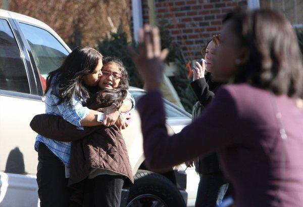 A woman hugs her daughter after being reunited following a mass shooting at the Sandy Hook Elementary School in Newtown, Conn., on Friday.