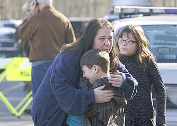 A young boy is comforted outside Sandy Hook Elementary School after a shooting in Newtown, Conn. on Friday.