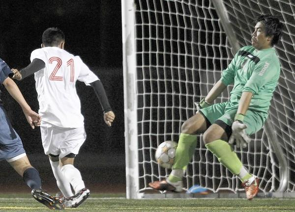Kevin Pizarro (21) of Estancia High chips the ball in past Newport Harbor goalie Osiel Porayo on Wednesday.