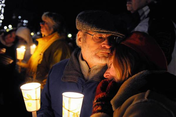 Win Heimer of West Hartford lends a shoulder to JoAnne Bauer of Hartford during a candlelight vigil at Hartford's Bushnell Park  in memory of and prayers for the students and teachers who died at Sandy Hook Elementary School in Newtown earlier in the day.